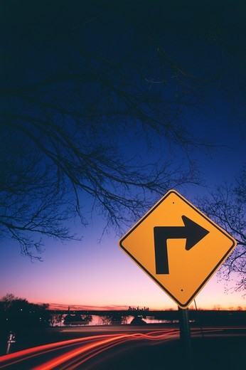 Neon streak of traffic and a sign with right directional arrow at roadside near a lake, White Rock Lake, Dallas, Texas, USA : Stock Photo