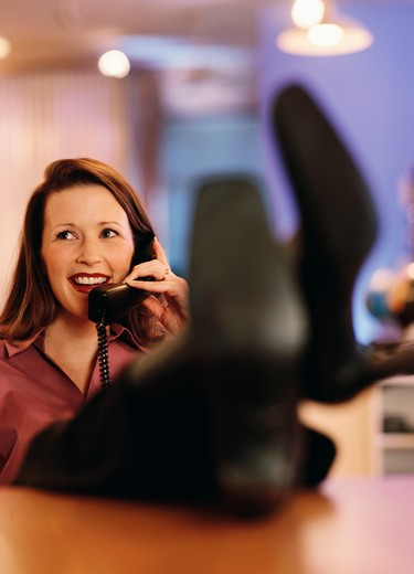Businesswoman talking on the telephone in an office : Stock Photo