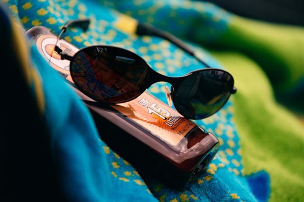 Sunglasses and suntan lotion on a beach towel : Stock Photo