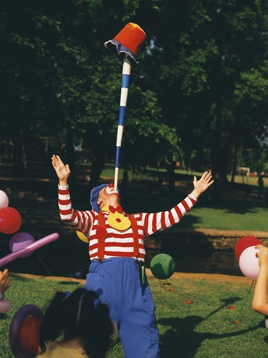 Clown performing a balancing trick with a pole and a bucket in a birthday party : Stock Photo