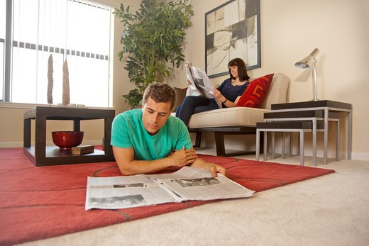 Couple relaxing at home, reading newspaper : Stock Photo