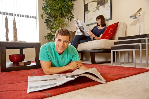 Stock Photo: 4009R-394 Couple relaxing at home, reading newspaper