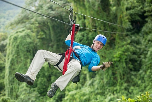Stock Photo: 4011-1159 Man riding a zip line in a forest, Costa Rica