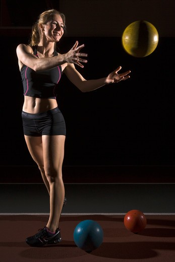Stock Photo: 4011-725 Young fit woman throwing weight ball