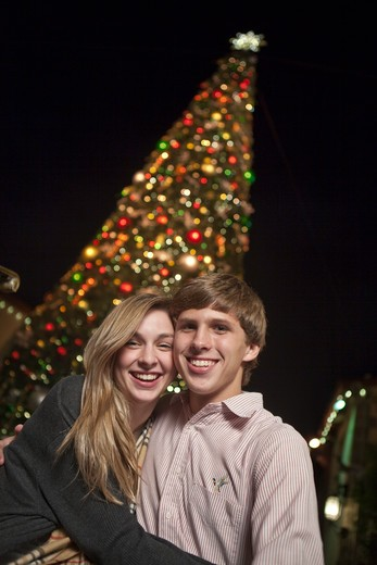 Stock Photo: 4011-766 Teenage couple standing in front of a Christmas tree and smiling