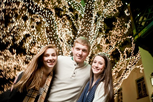 Stock Photo: 4011-767 Teenage friends standing in front of a Christmas tree