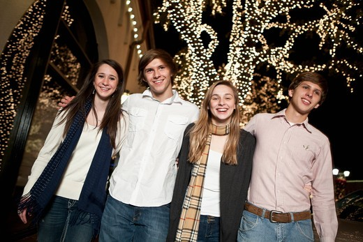 Stock Photo: 4011-793A Four teenage friends standing in front of a Christmas tree and smiling