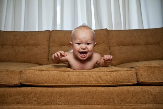 Seven month old baby on couch laughing : Stock Photo