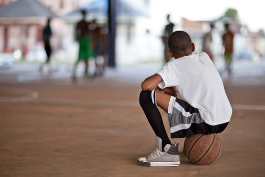 Young boy watching basketball game : Stock Photo