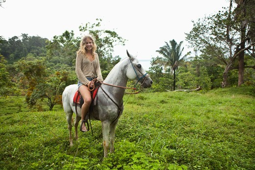 Woman riding a horse in the rainforest, Costa Rica : Stock Photo