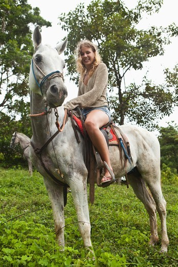 Stock Photo: 4011-965 Woman riding a horse in the rainforest, Costa Rica
