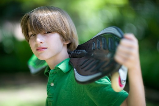 Stock Photo: 4011R-393B Boy holding a ripstik in a park, Texas, USA