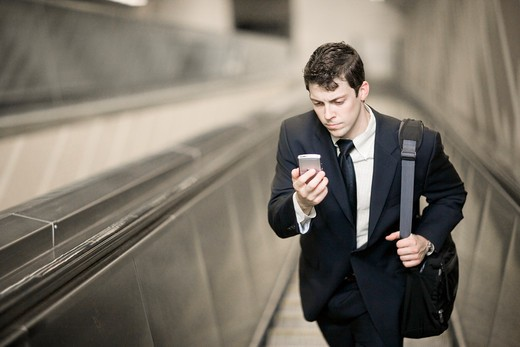 Stock Photo: 4011R-471G Businessman on escalator with cell phone