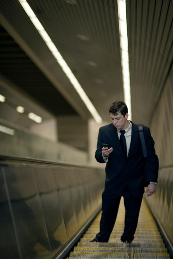 Stock Photo: 4011R-471I Businessman on escalator with cell phone