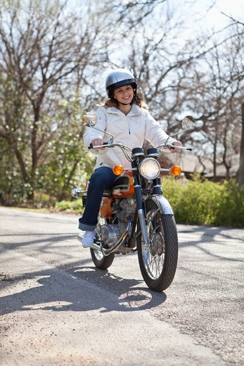 Teenage girl riding motorcycle : Stock Photo