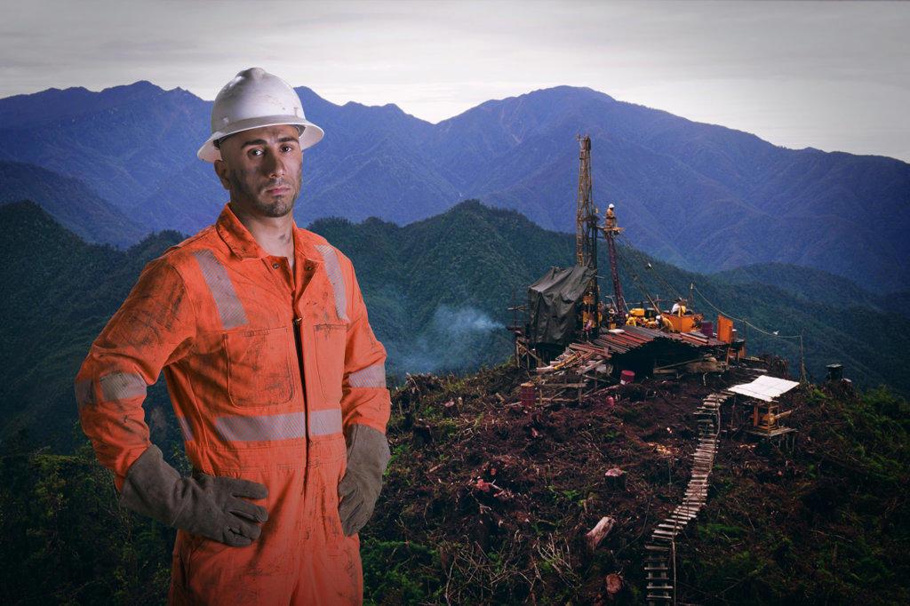 Stock Photo: 4013-115 Oil drilling platform worker standing above the oil platform