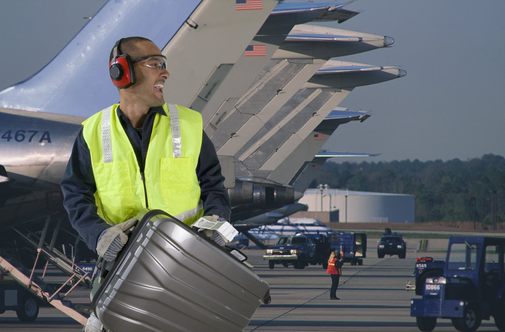 Stock Photo: 4013-126 Airport baggage employee loading luggage in an airplane