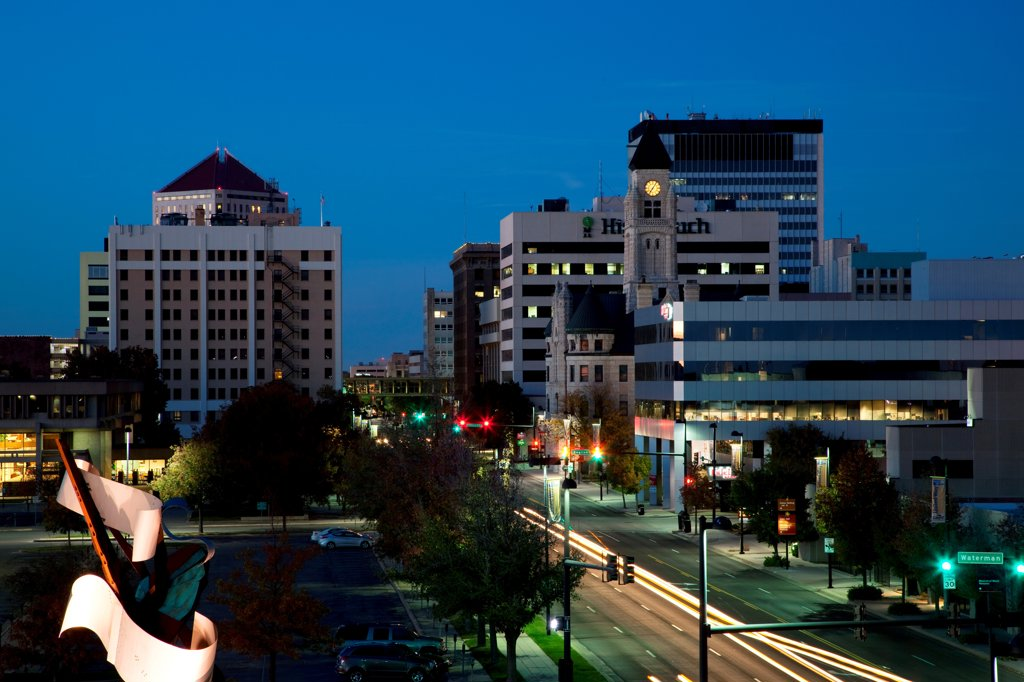 Stock Photo: 4017-3829 USA, Kansas, Wichita, Downtown at dusk with Main Street traffic and Waterwalk Sculpture