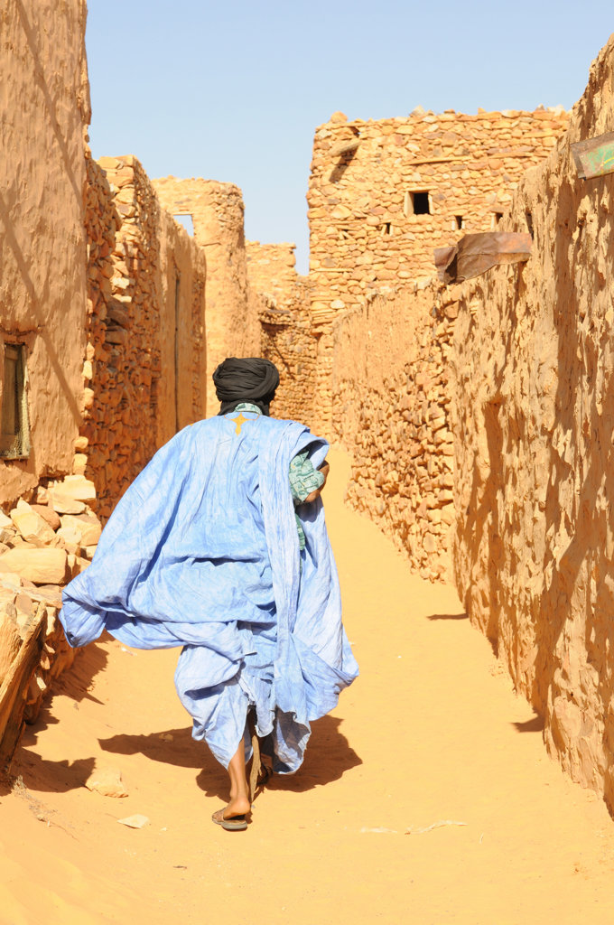 Mauritania, Chinguetti, man walking through sandy lanes of town : Stock Photo