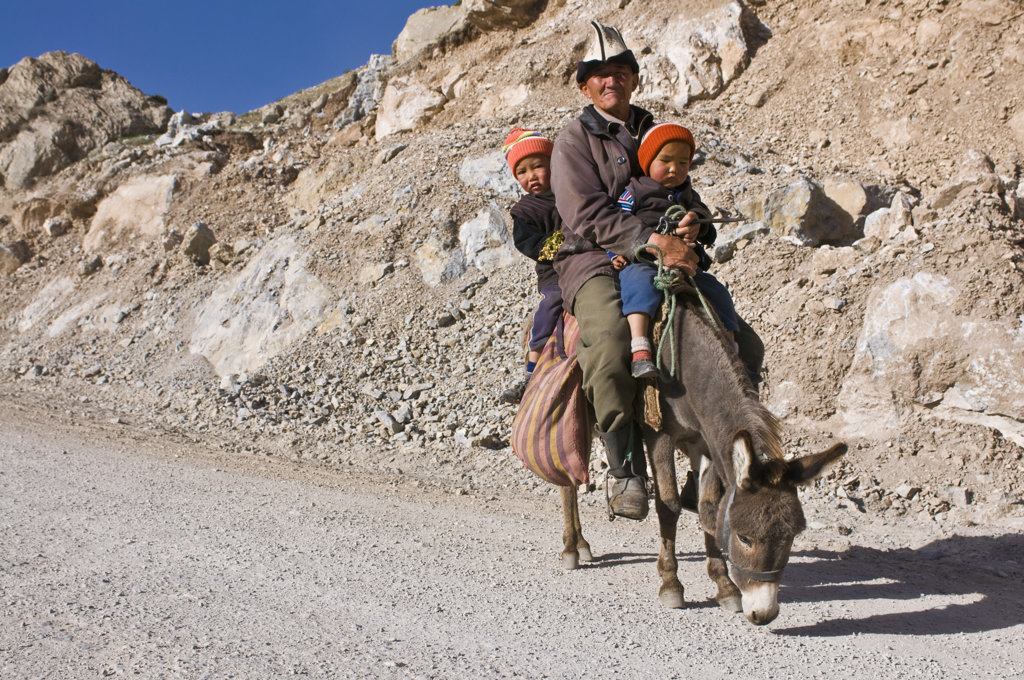 Stock Photo: 4021-2881 Kyrgyzstan, Osh Province, Grandfather with grandchildren riding donkey between Sary Tash and Osh