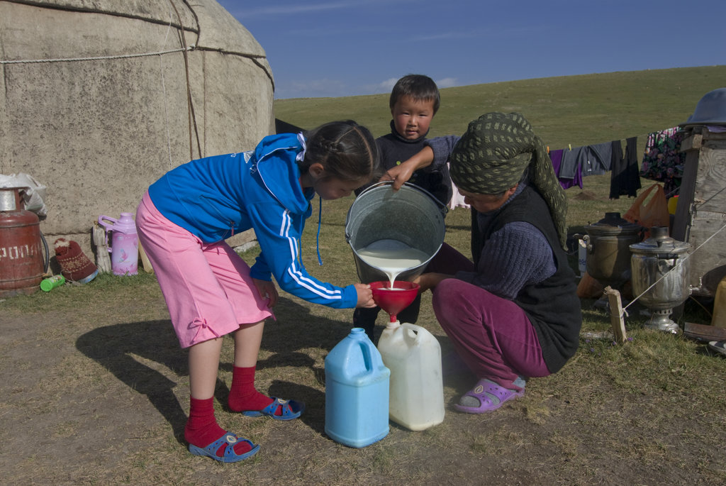 Kyrgyzstan, Song Kol, Mother with children pouring milk into plastic containers : Stock Photo