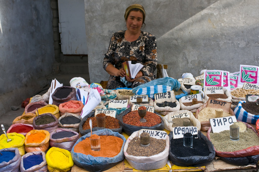 Kyrgyzstan, Osh, Market vendor selling colorful spices : Stock Photo
