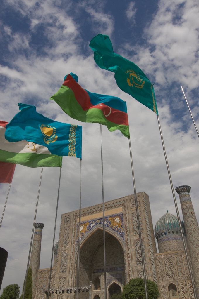 Uzbekistan, Samarkand, Registan, Flags flying before Mosque : Stock Photo