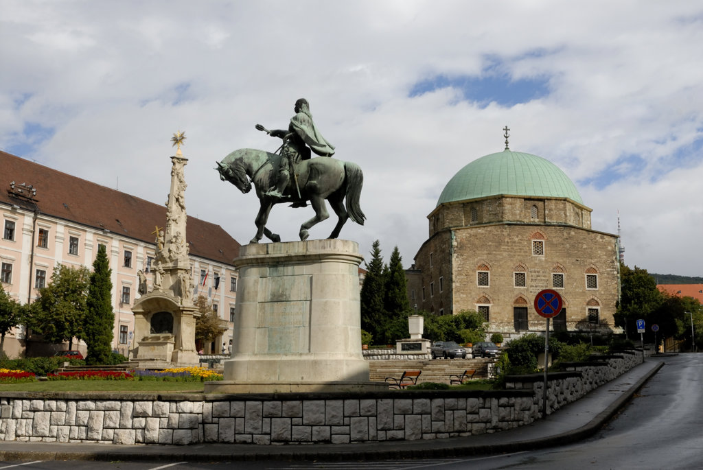 Equestrian statue with a church in the background, Mosque Of Pasha Qasim, Szechenyi Square, Pecs, Baranya County, Hungary : Stock Photo