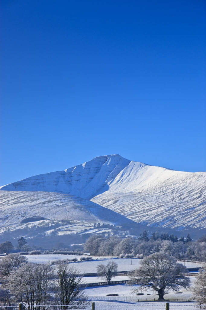Snow covered field with mountain range in the background, Pen Y Fan, Corn Du mountains, Mynydd Illtyd Common, Brecon Beacons National Park, Powys, Wales : Stock Photo