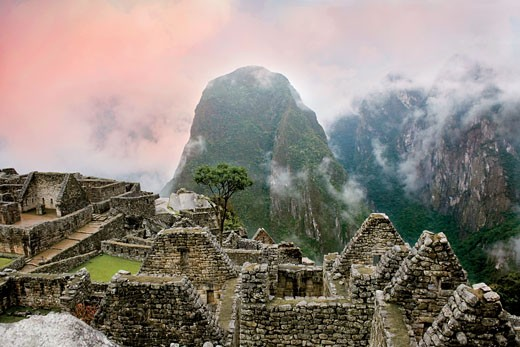 Stock Photo: 4028-1167 Peru, Machu Picchu, the ancient lost city of the Inca shrouded in mist and clouds at sunrise.