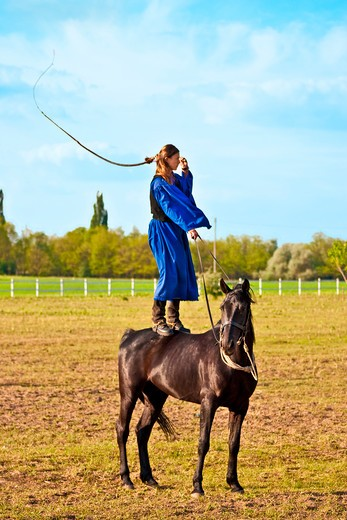 Hungary, Kalocsa, female Csikos Hungarian horse rider, standing on a horse as she demonstrates prowess with her whip : Stock Photo