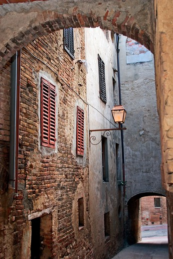 A courtyard opens up to the narrow streets and alleyways near the Piazza del Duomo in San Gimignano, Tuscany. : Stock Photo