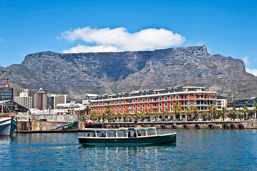 Cape Town, South Africa, A water taxi sails by the The Victoria and Albert waterfront with Table Mountain in the background : Stock Photo
