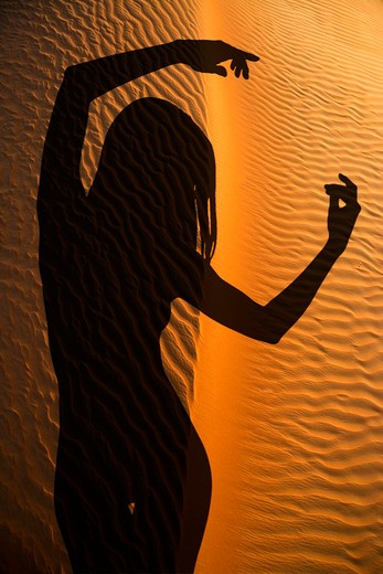 Silhouette shadow of a belly dancer in a dance club imposed over an image of the Arabian Desert near Dubai, United Arab Emirates : Stock Photo