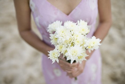 A woman holding bouquet of flowers : Stock Photo