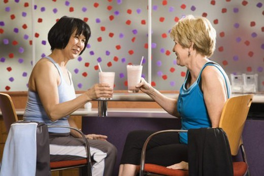 Mature Asian and Caucasian adult females sitting at table in health club cafeteria. : Stock Photo