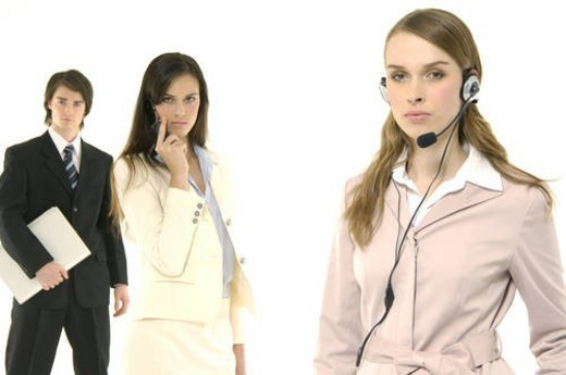 Portrait of a female customer service representative talking on a headset with her colleagues standing behind her : Stock Photo