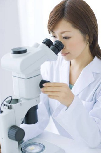 Stock Photo: 4029R-10281 Woman looking through microscope