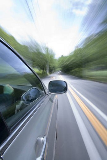 Car driving along a tree lined road : Stock Photo