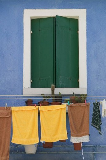 Green window shutters on blue painted building, with laundry on clothes line : Stock Photo