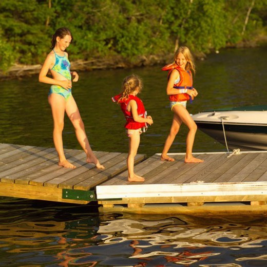 Three girls standing on a pier in swimsuits : Stock Photo