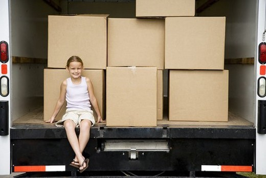 Little girl sitting with packing boxes in the removal van, moving home : Stock Photo