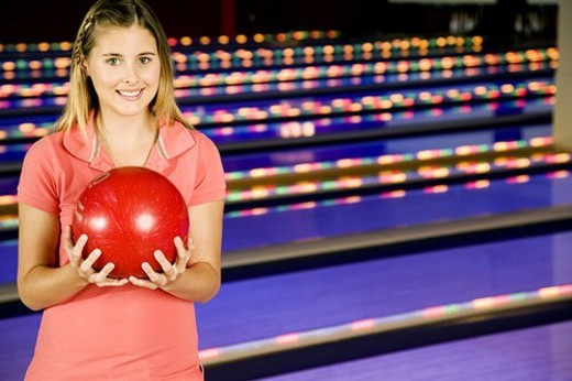 Stock Photo: 4029R-105698 Teenage girl in bowling alley holding a red bowling ball