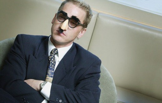Stock Photo: 4029R-107930 Serious businessman wearing Groucho Marx mask disguise