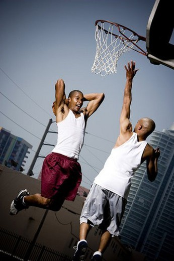 Stock Photo: 4029R-108001 Two Young African American man jumping with a basketball on an urban basketball court