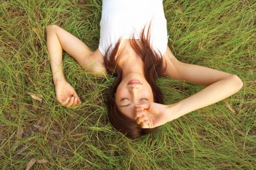 Young woman lying on grass, eyes closed : Stock Photo