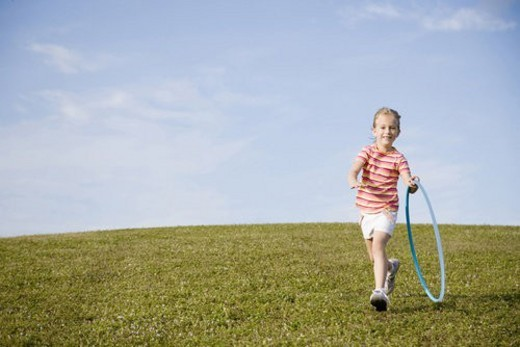 A Young girl chasing a hoop : Stock Photo