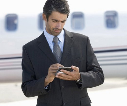 Stock Photo: 4029R-112793 A businessman standing by a plane
