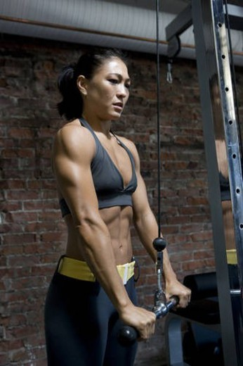 Asian girl training in a gym with weights : Stock Photo