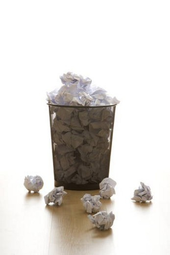 Stock Photo: 4029R-115116 Full wire mesh trash can with crumpled paper scattered around.